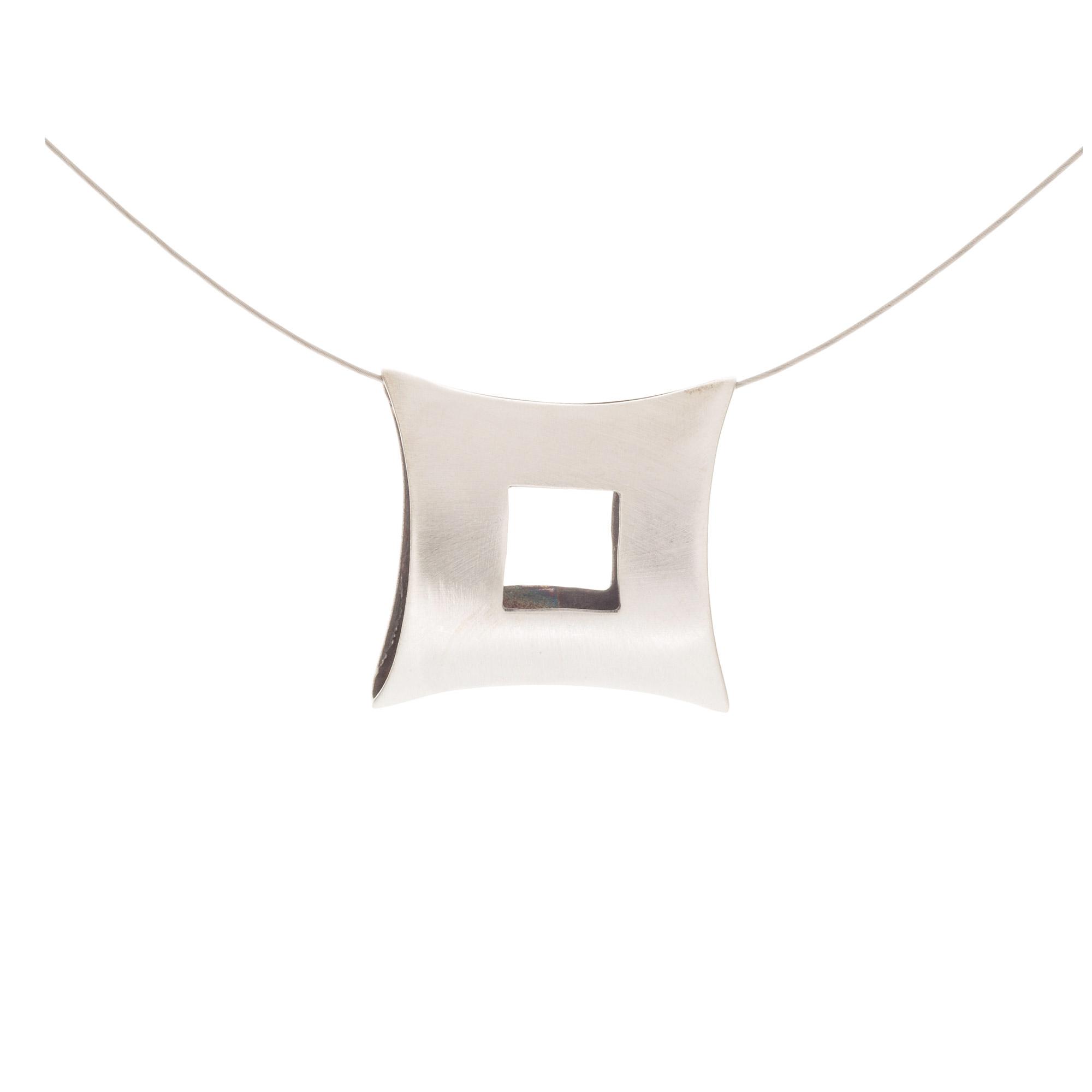 Colgante hecho a mano en plata, oxidado y acabado en mate. Cadena de acero cubierta con una capa de nylon, cierre de plata.